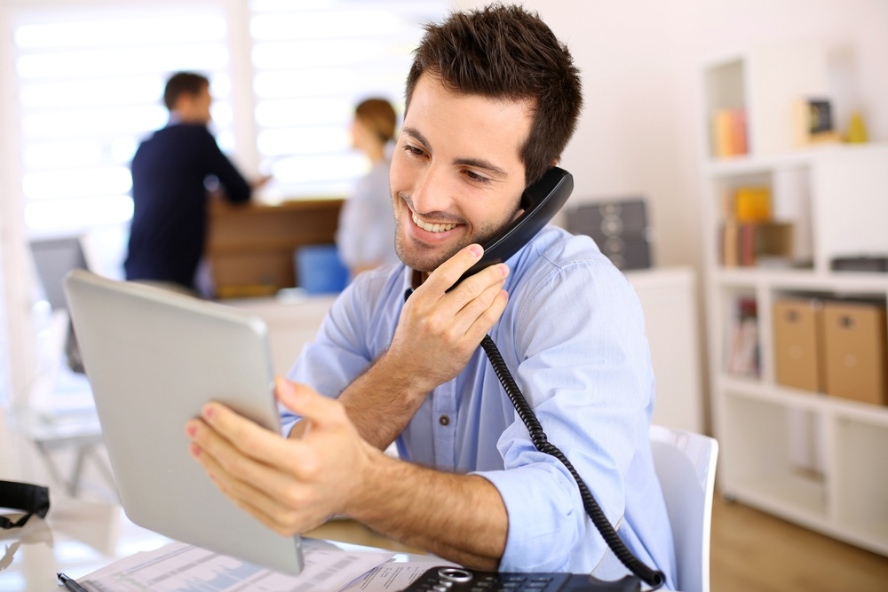 Cheerful man in office answering the phone.jpeg