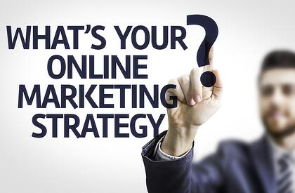 Business man pointing to transparent board with text What's your Online Marketing Strategy?.jpeg