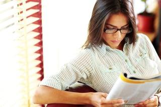Businesswoman reading magazine in modern office.jpeg