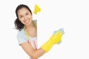 Cheerful woman cleaning white surface in apron and rubber gloves