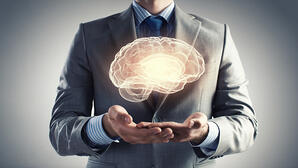 Close up of businessman holding digital image of brain in palm-1