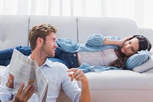 Couple relaxing in the living room listening to music and reading a newspaper-1