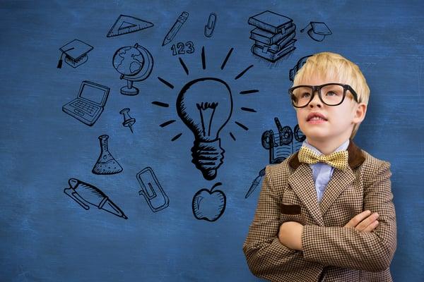 Cute pupil dressed up as teacher against blue chalkboard