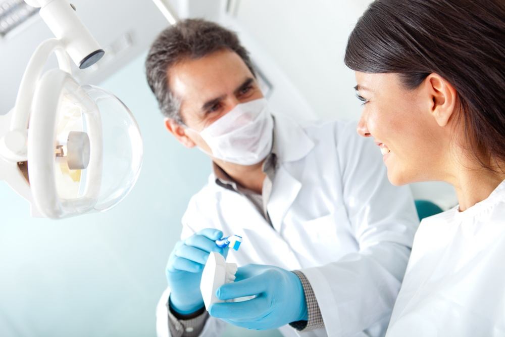 Dentist showing a woman how to brush her teeth on prosthesis