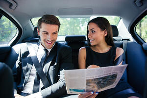 Happy couple reading newspaper in car-1