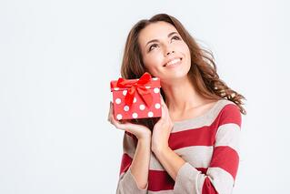 Portrait of a happy thoughtful woman holding gift box and looking up isolated on a white background.jpeg