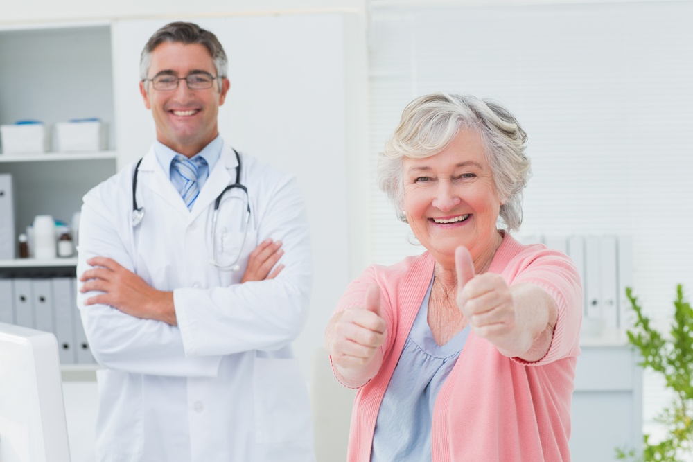 Portrait of happy female patient showing thumbs up sign while standing with doctor in clinic