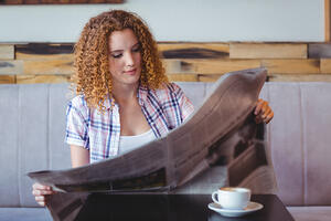 Pretty curly hair girl having cup of coffee and reading newspaper at the cafe-1