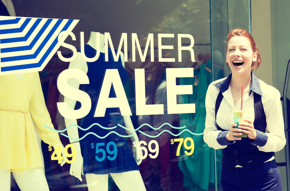 Shopping time sale event. Beautiful young woman standing outside in front of store display window, summer price reduction sign excited laughing. Positive human emotion face expression. Summer spree