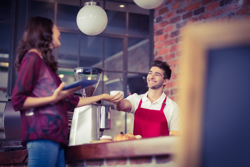 Smiling waiter serving a client at the coffee shop.jpeg