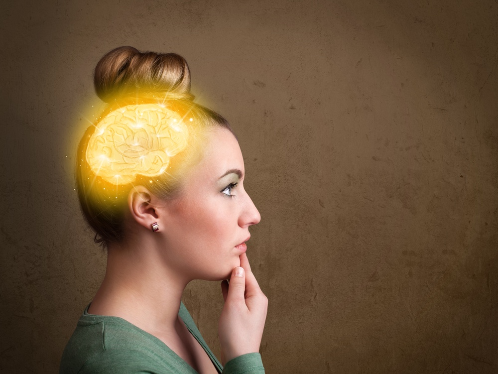 Young girl thinking with glowing brain illustration on grungy background.jpeg